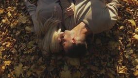 Привлекательная европейская белокурая девушка, и красивый молодой человек в свитерах Молодые пары лежа на листьях осени на акции видеоматериалы