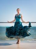 Привлекательная девушка в стильном синем платье Чувственная женщина на предпосылке голубого неба Красивое, ослабляющ и Стоковое Фото