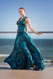 Привлекательная девушка в стильном синем платье Чувственная женщина на предпосылке голубого неба Красивое, ослабляющ и Стоковые Изображения