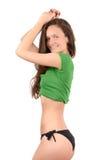 Привлекательная девушка в черном бикини и зеленая верхняя часть представляя от профиля показывая ее кривые. Стоковые Фотографии RF