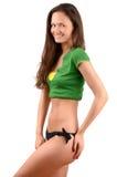 Привлекательная девушка в черном бикини и зеленая верхняя часть представляя от профиля показывая ее кривые. Стоковые Фото