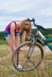 Привлекательная девушка надувая колесо велосипеда Стоковая Фотография