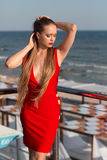 Привлекательная девушка представляя на террасе на голубой предпосылке моря Сексуальная дама в красном платье Женщина с изумительн стоковое изображение rf