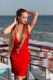 Привлекательная девушка представляя на террасе на голубой предпосылке моря Сексуальная дама в красном платье Женщина с изумительн стоковые фотографии rf
