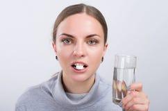 Привлекательная девушка принимая пилюльку с водой на светлой предпосылке Стоковые Изображения