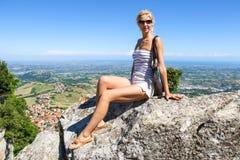 Привлекательная девушка сидит на камне в крепости Сан-Марино стоковые изображения rf