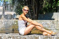 Привлекательная девушка сидит фонтаном в старом парке города стоковое изображение rf