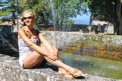 Привлекательная девушка сидя фонтаном в старом парке города стоковое фото