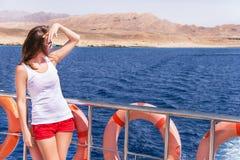 Привлекательная девушка стоящая и ослабляющ на яхте Стоковая Фотография