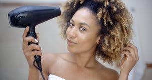 Привлекательная девушка сушит волосы стоковая фотография