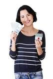 Привлекательная девушка с деньгами и дом на руках. Стоковая Фотография