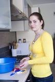 Привлекательная девушка с одежд-шпеньками на кухне Стоковое Фото