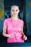 Привлекательная девушка фитнеса бежать на третбане машины Милая девушка делая разминку на современном спортзале фитнеса Стоковые Изображения RF