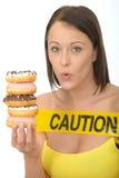 Привлекательная естественная молодая женщина держа кучу Donuts Iced с осторожностью подписывает Стоковые Фото