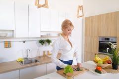 Привлекательная женская домохозяйка режет огурец с ножом и улыбками, Стоковое фото RF