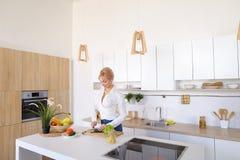Привлекательная женская домохозяйка режет огурец с ножом и улыбками, Стоковая Фотография RF