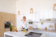 Привлекательная женская домохозяйка режет огурец с ножом и улыбками, Стоковая Фотография
