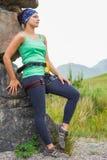 Привлекательная женская склонность альпиниста утеса на стороне утеса Стоковое Фото