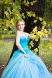 Привлекательная женщина в длинном голубом платье в парке blondish стоковые изображения rf