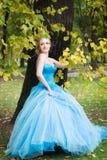 Привлекательная женщина в длинном голубом платье в парке blondish стоковая фотография rf