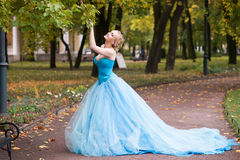 Привлекательная женщина в длинном голубом платье в парке blondish стоковые фотографии rf