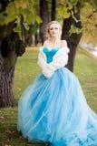 Привлекательная женщина в длинном голубом платье в парке blondish стоковые изображения