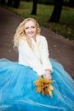Привлекательная женщина в длинном голубом платье в парке blondish стоковое фото