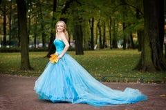 Привлекательная женщина в длинном красном платье в парке blondish стоковое фото rf