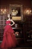 Привлекательная женщина в длинном красном платье в роскошном интерьере ретро, винтажный стиль Стоковое фото RF
