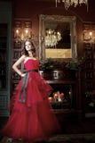 Привлекательная женщина в длинном красном платье в роскошном интерьере ретро, винтажный стиль Стоковое Изображение RF