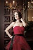 Привлекательная женщина в длинном красном платье в роскошном интерьере ретро, винтажный стиль Стоковые Фото