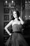 Привлекательная женщина в длинном красном платье в роскошном интерьере ретро, винтажный стиль Стоковые Изображения