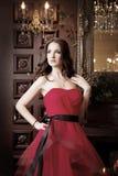 Привлекательная женщина в длинном красном платье в роскошном интерьере ретро, винтажный стиль Стоковые Фотографии RF