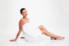 Привлекательная женщина в полотенце сидя на поле стоковые фотографии rf