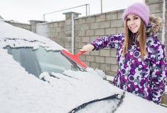 Привлекательная женщина в правом автомобиле чистки куртки от снега Стоковые Изображения