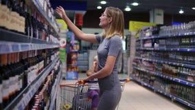 Привлекательная женщина в стеклах выбирает бутылку вина в отделе напитков в супермаркете, пока ее маленькое сток-видео