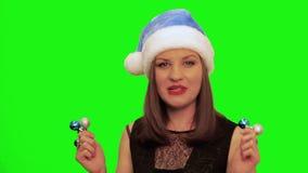 Привлекательная женщина в шляпе santa танцует и поет песня xmas против зеленого экрана chromakey сток-видео