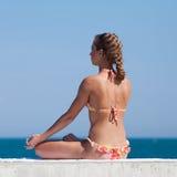 Привлекательная женщина в swimwear делая йогу на море стоковые изображения