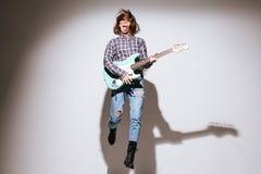Привлекательная женщина держа гитару над белыми предпосылкой и скакать Стоковое Фото