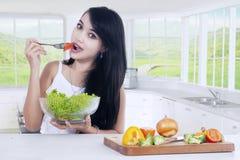Привлекательная женщина есть здоровый салат дома Стоковое Изображение