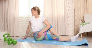 Привлекательная женщина делает фитнес протягивая дома интерьер в живущей комнате Стоковая Фотография