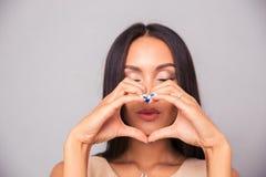 Привлекательная женщина делая сердце с пальцами Стоковая Фотография
