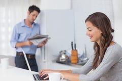 Привлекательная женщина используя ее компьтер-книжку в кухне Стоковое фото RF