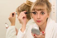 Привлекательная женщина используя карандаш для глаз туши Стоковые Фотографии RF
