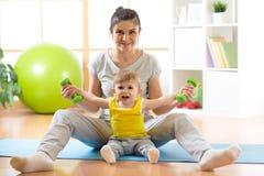 Привлекательная женщина и ее мальчик ребенка работая с гантелями Стоковое Изображение
