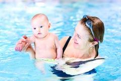 Привлекательная женщина и милый ребёнок в бассейне Стоковая Фотография