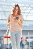 Привлекательная женщина идя вниз с улицы и используя умный телефон Стоковые Изображения