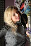 Привлекательная женщина поя в студии звукозаписи Стоковое Изображение