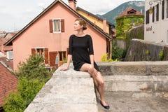 Привлекательная женщина представляя на предпосылке европейских домов Стоковые Изображения RF