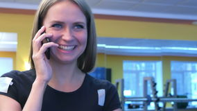 Привлекательная женщина пригонки говоря на телефоне пока идущ на третбан видеоматериал